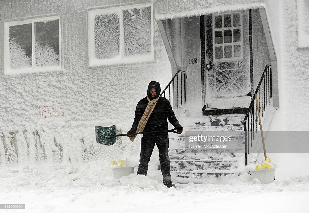 A man shovels snow along Winthrop Shore Drive February 9, 2013 in Winthrop, Massachusetts. The powerful storm has knocked out power to 650,000 and dumped more than two feet of snow in parts of New England.