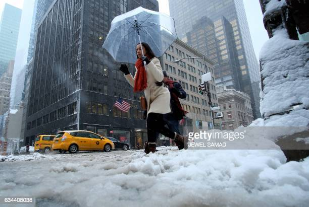 TOPSHOT A man shovels snow from a street during a winter storm in New York on February 9 2017 A heavy winter snow storm lashed the northeastern...