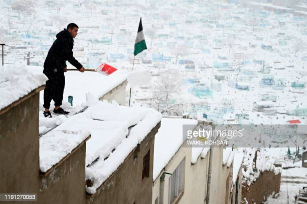 A man shovels snow from the roof of his house in Kabul on January 2 2020