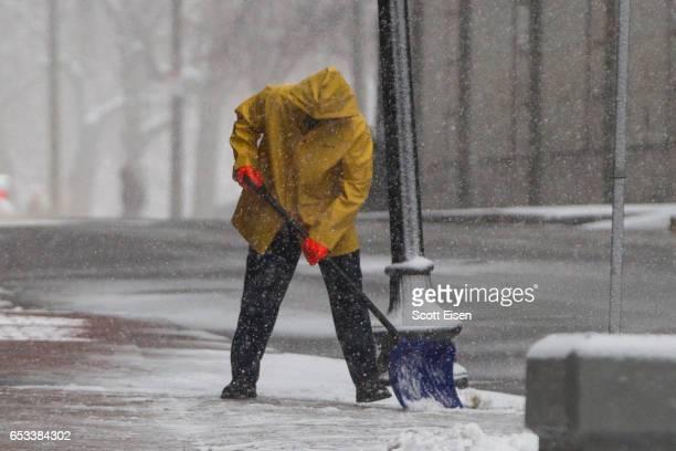 A man shovels snow from the sidewalk as Winter Storm Stella bears down on March 14 2017 in Boston Massachusetts