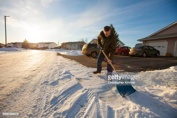 a man shovels snow in northern alberta. - shovel stock pictures, royalty-free photos & images