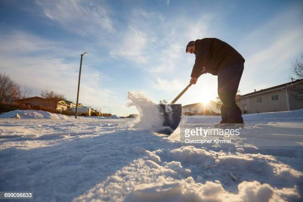 A man Shovels snow in northern Alberta.