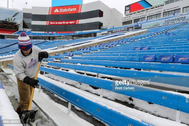 A man shovels snow out of the stands before a game between the Indianapolis Colts and Buffalo Bills on December 10 2017 at New Era Field in Orchard...