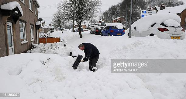 A man shovels snow outside his house in Mold Flintshire north Wales on March 23 2013 Heavy unseasonal snow caused fresh disruption in Britain on...