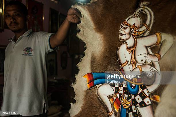 A man show puppets wall decoration picture in Wukirsari Imogiri Bantul Yogyakarta Indonesia on May 23 2016 Shadow puppets are made of buffalo skin an...