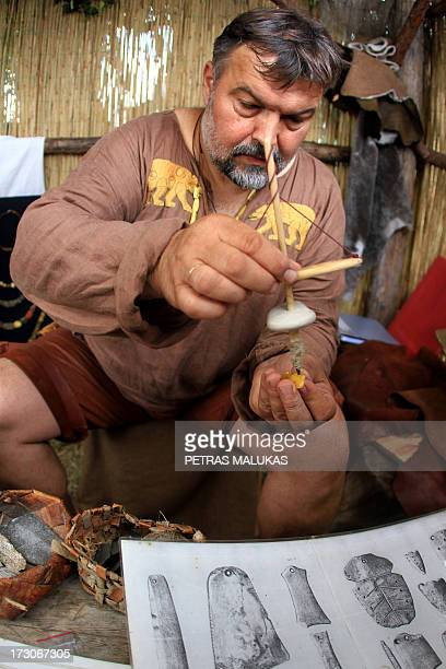 A man showcases an ancient amber drilling method during the experimental archeology festival 'Days of Live Archaeology in Kernave' in the old capital...