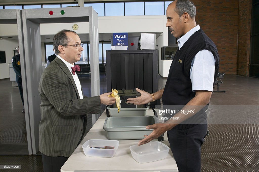 Man Showing a Half Eaten Banana to an Unimpressed Customs Officer in an Airport : Stock Photo