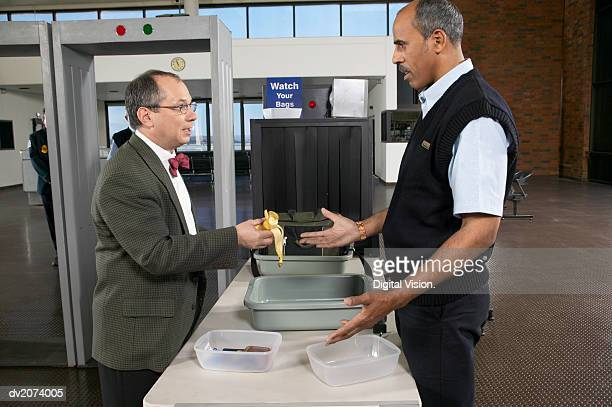 Man Showing a Half Eaten Banana to an Unimpressed Customs Officer in an Airport