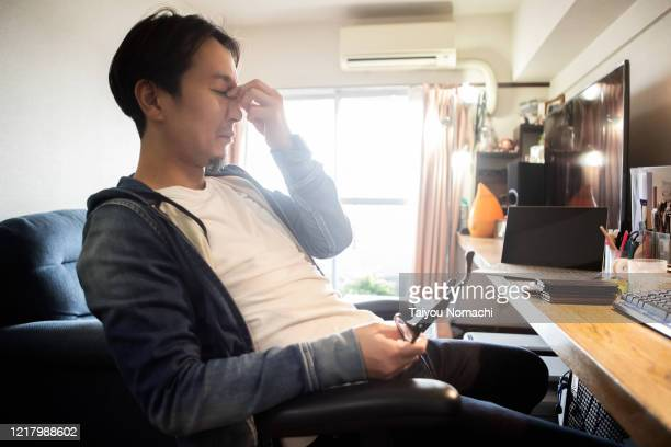 a man showing a tired expression while working from home - medical condition ストックフォトと画像