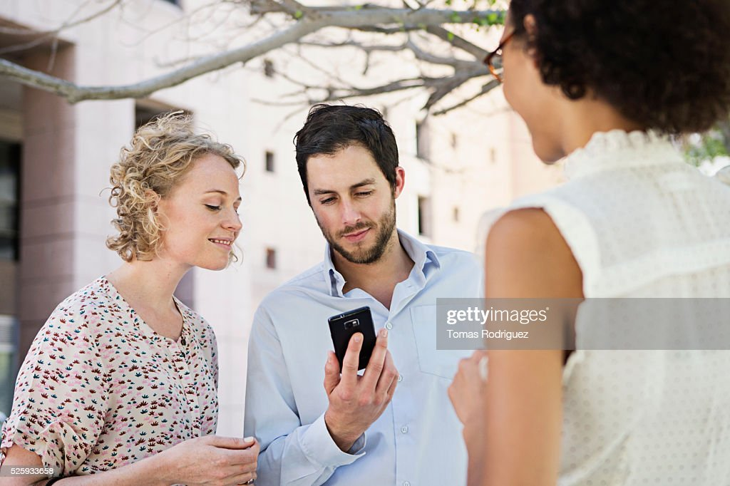 Man showing cell phone to women : Foto de stock
