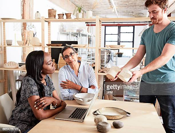 Man showing colleagues ceramic samples