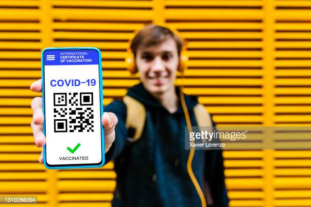 man showing covid-19 vaccination certificate on mobile phone screen - certificate stock pictures, royalty-free photos & images
