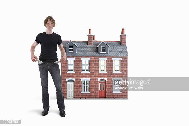 man showing empty pockets in front of model house - ドールハウス ストックフォトと画像