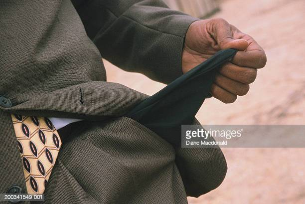 Man showing empty trouser pocket, mid section