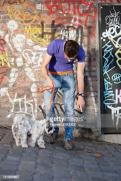 man showing feces to his puppy, paris, ile-de-france, france - cacca foto e immagini stock