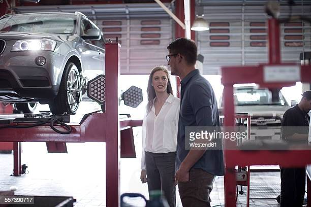 Man showing female customer the tyre fitment process