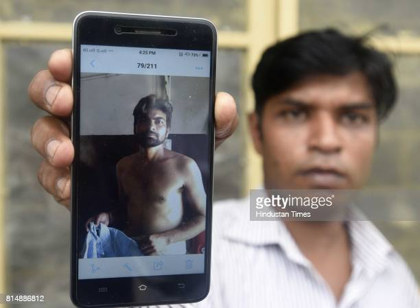 A man showing file photo of Deepu who was died during the septic tank cleaning at Ghiloni in Chattarpur area on July 15 2017 in New Delhi India Four...