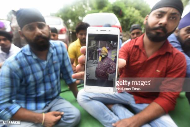 A man showing file photo of Gurmej Singh son of Swaran Singh who was died during the septic tank cleaning at Ghiloni in Chattarpur area on July 15...