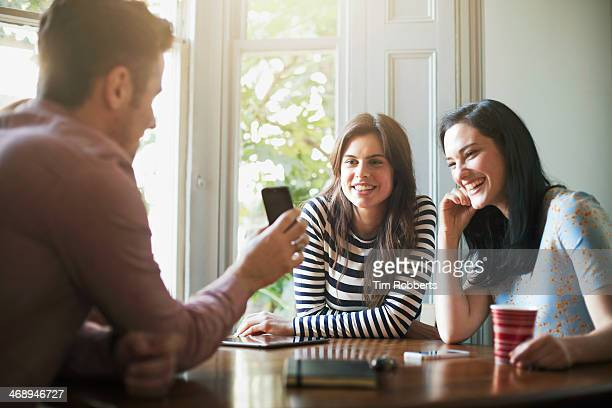 Man showing his friends a photo on his smart phone