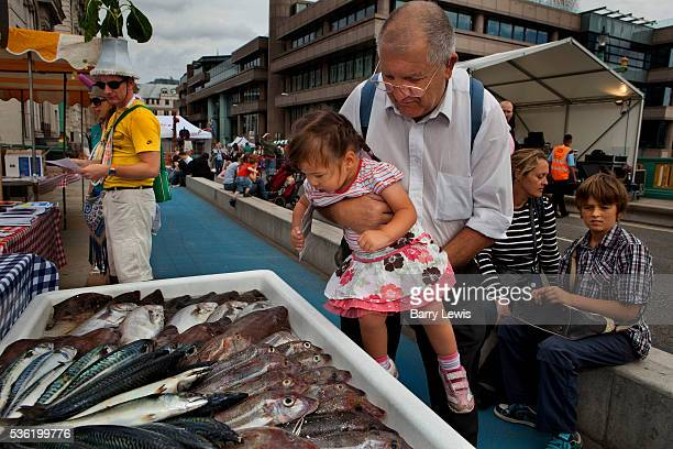 Man showing his grandchild fresh fish on a stall on Southwark Bridge which is transformed into a giant banqueting space, designed by Cathy Wren, with...