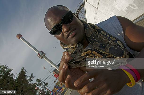 Man showing his pet snakes on the boardwalk of Coney Island, shortly before Hurricane Sandy devastated the community. Smiles and the exotica have...