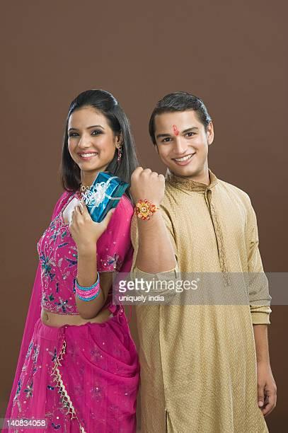 man showing his rakhi with his sister showing her present - raksha bandhan stock photos and pictures