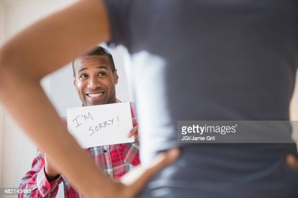 Man showing 'I'm Sorry' sign to angry girlfriend