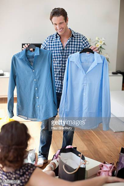 man showing new shirts to wife - all shirts stock pictures, royalty-free photos & images