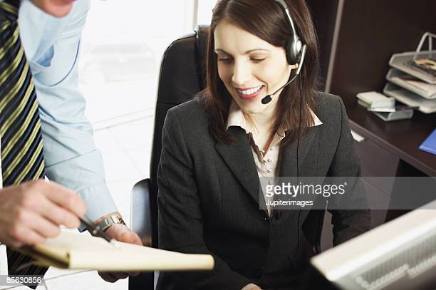 Man showing notepad to woman wearing headset