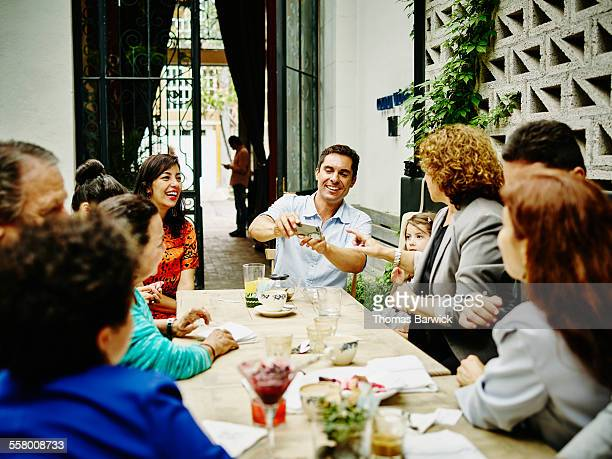 Man showing smartphone to family during dinner