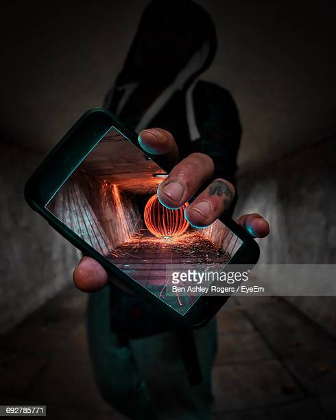 man showing wire wool on smart phone screen in tunnel - foco no primeiro plano - fotografias e filmes do acervo