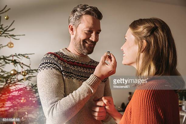 Man showing woman engagement ring by Christmas tree