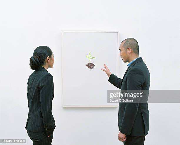 Man showing woman picture in art gallery