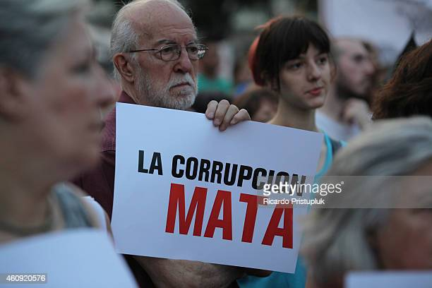 A man shows a banner during a rally in memory of the victims of Cromanon's tragedy at Plaza de Mayo on December 30 2014 in Buenos Aires Argentina...