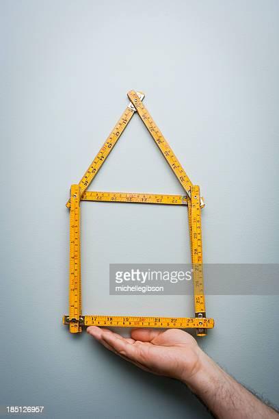 Mann zeigt ein Zollstock in der Form eines Hause