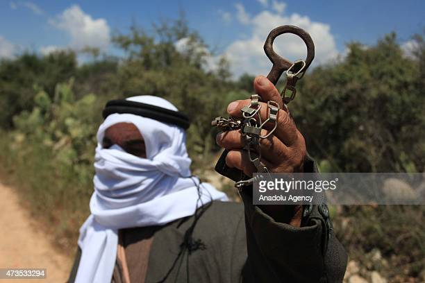 A man shows a lock which represents his demolished house as Palestinians mark the 67th anniversary of the 'Nakba' at the Nalin region in Ramallah...