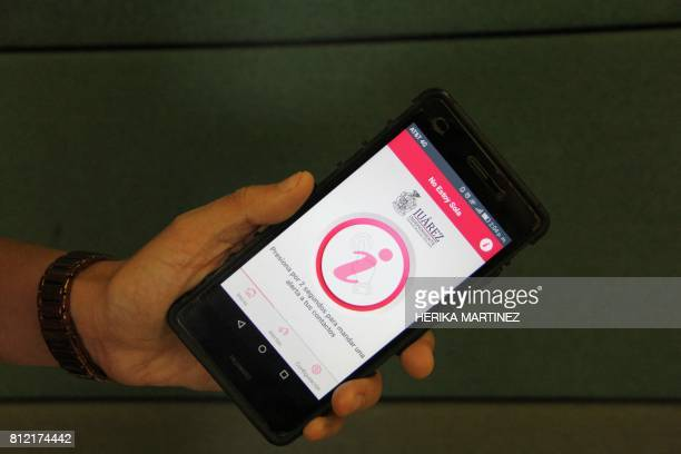 A man shows a new app released by Ciudad Juarez's municipality to help women in risk send alert calls in Ciudad Juarez Mexico on July 10 2017 The...