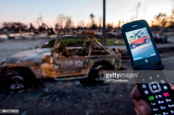 A man shows a photo of his Jeep on his cell phone before it burned in Santa Rosa California on October 20 2017 Residents are being allowed to return...