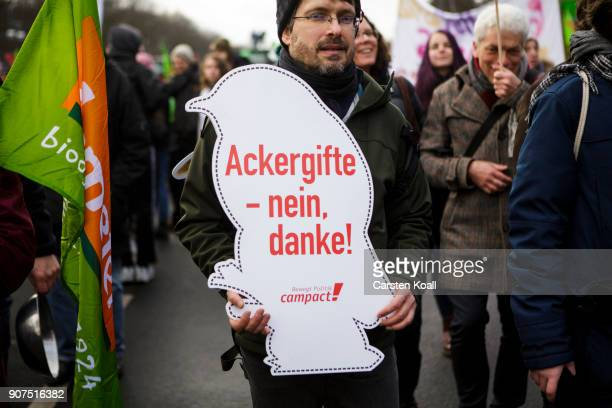 A man shows a sign with the written words 'ground poisons no thanks' march to demonstrate against the agroindustry on January 20 2018 in Berlin...