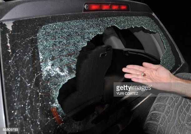 A man shows a smashed bullet found inside the car used by AFP photographer Yuri Cortez and local photographer Carlos Aviles during the covering of...