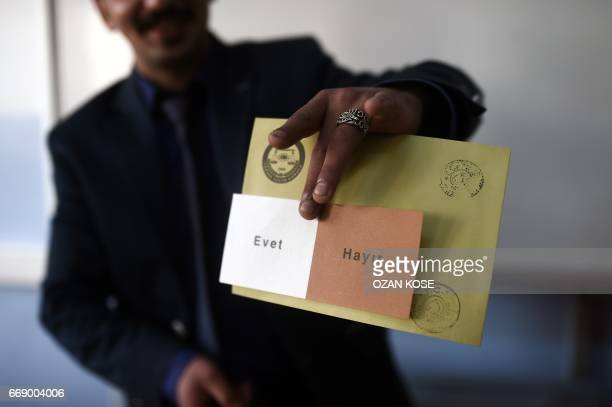 A man shows a voting ballot with the words in Turkish that read 'Evet' or Yes and 'Hayir' or No as people vote in the referendum on expanding the...