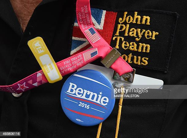 A man shows a 'We Want Bernie' badge from the Presidential campaign of Bernie Sanders but jokingly telling people it was about F1 boss Bernie...