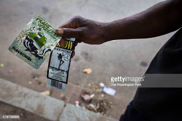 Man shows an empty packet of Show cigars and Train Wrecked, a brand of what is commonly referred to as K2 or spice, nearby the corner of 2nd and D...