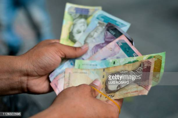 Man shows Bolivar bills he will use to make handicrafts in a street of Cucuta, Colombia, on the border with Venezuela, on February 20, 2019. - The...