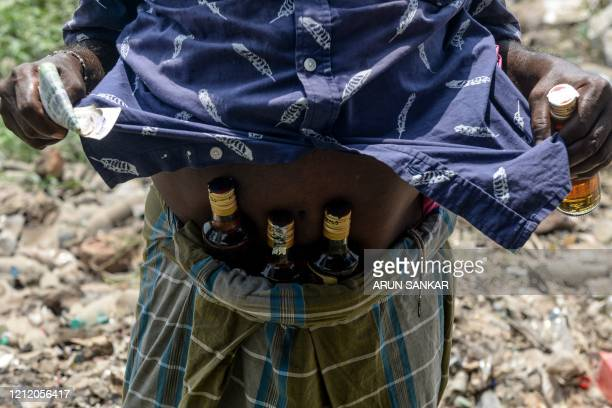 A man shows bottles of alcohol stuck under his waistband bought from a liquor shop after the government eased a nationwide lockdown imposed as a...