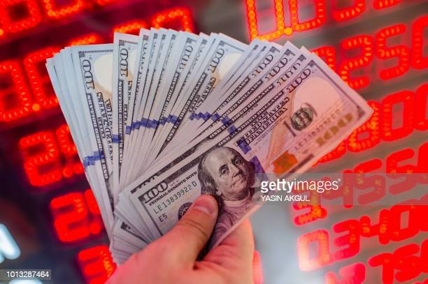 A man shows dollar banknotes at a currency exchange office in Istanbul on August 8 2018 The Turkish lira on August 1 slumped to record lows of 50...