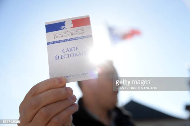 A man shows his electoral card near a polling station in the small rural town of Le Pin western France on April 23 2017 during the first round of the...