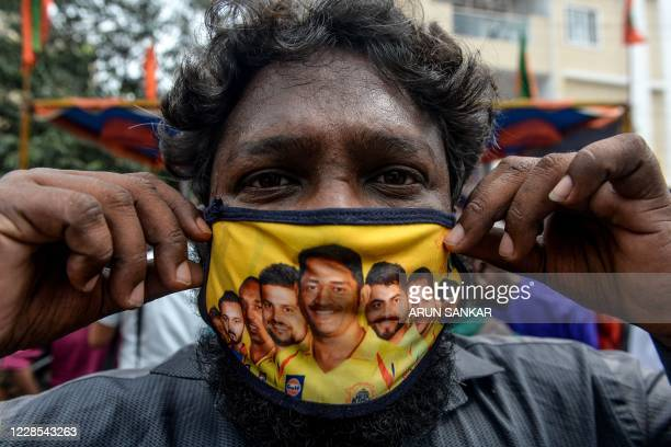 A man shows his facemask decorated with portraits of Chennai Super Kings cricket captain Mahendra Singh Dhoni and other team players as Covid19...