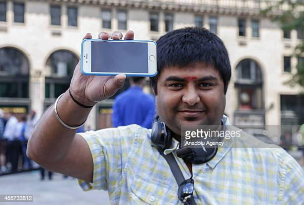 A man shows his iPhone as he exits the Apple store on Fifth Avenue after being one the first person purchasing the new iPhone 6 plus in New York...