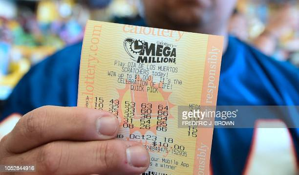 A man shows his just purchased lottery tickets from the Blue Bird Liquor store in Hawthorne California on October 23 2018 ahead of the drawing...